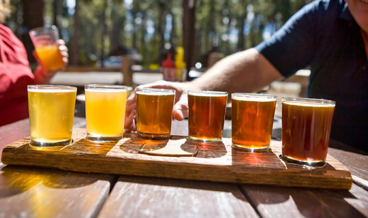 A taster tray of amber-colored beers sits on a picnic table outside.