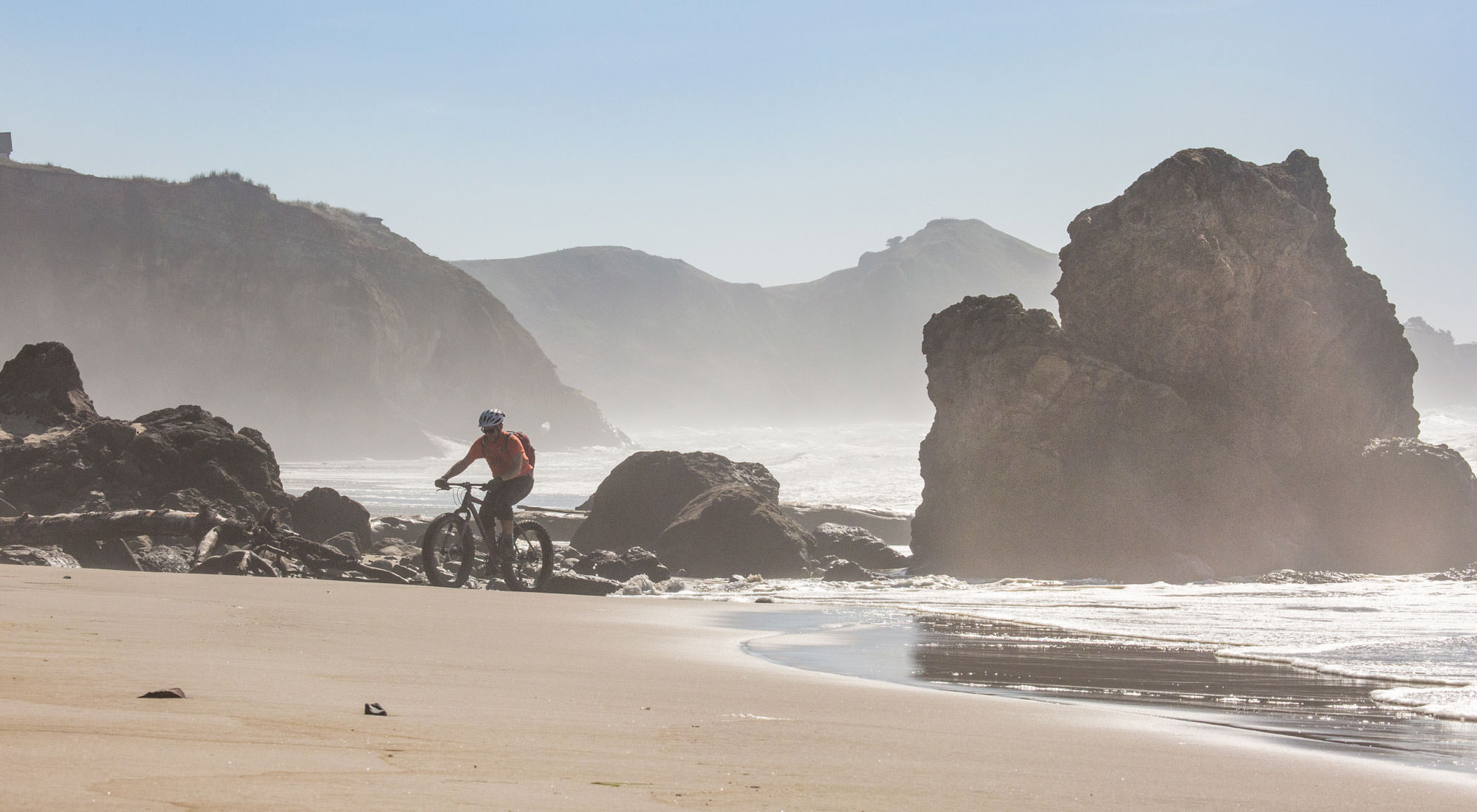 Man rides fat bike around large rock formations on the shoreline.