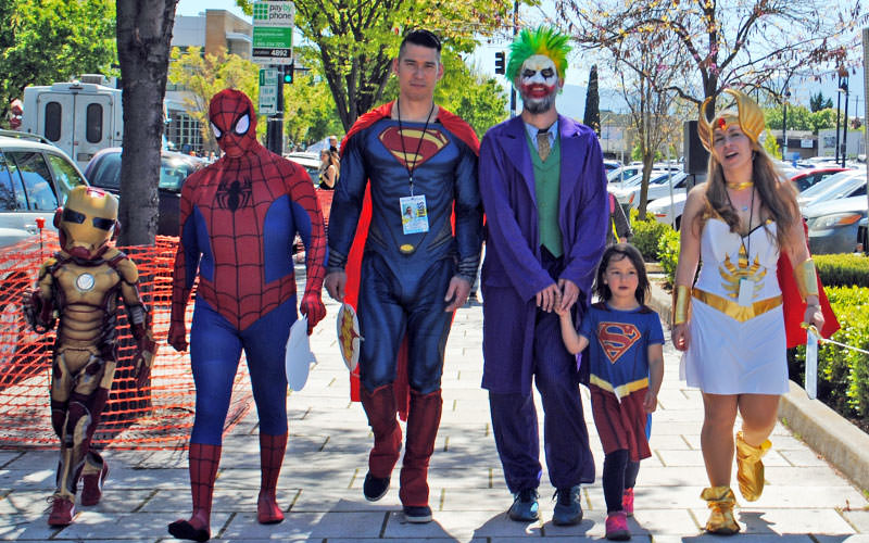 Family dressed like superheros Iron Man, Spiderman, Superman, The Joker, Supergirl and Lady Thor walk down the street in smiles.