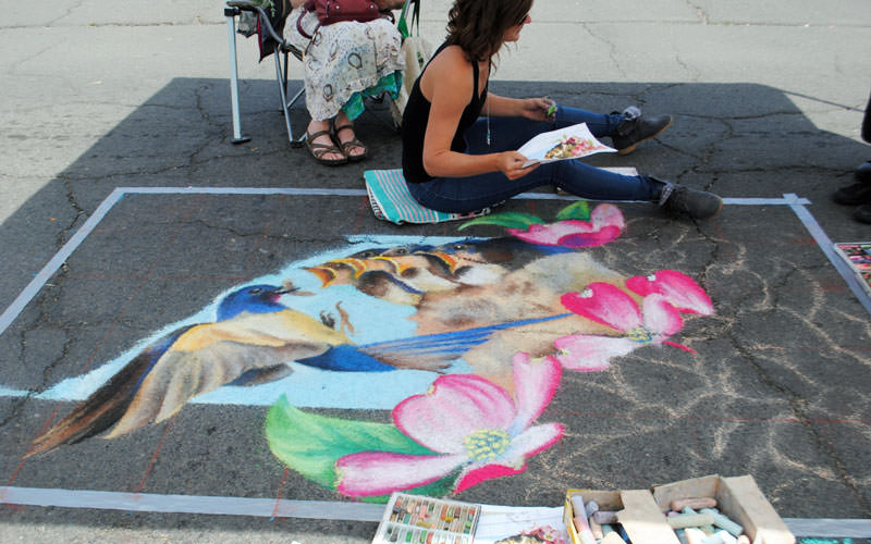 A chalk artist sits next to a realistic depiction of a mama bird feeding her chicks.