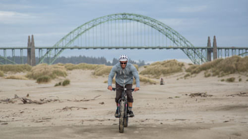 The green Newport Bridge looms in the background as a man gleefully rides a fat bike on the sand.