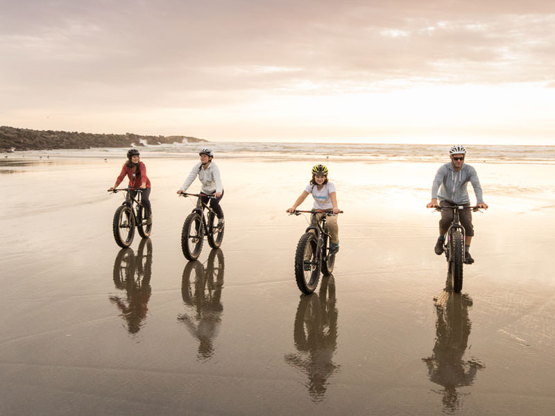 A family of four smiles for the camera while riding fat bikes at sunset.