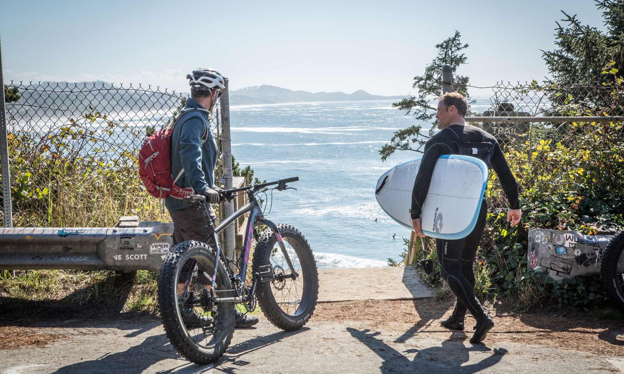Man holding a fat bike shares the sidewalk with a surfer.