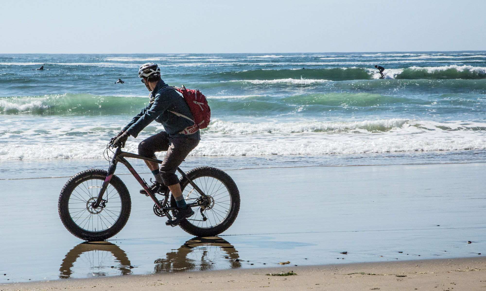 A man riding a fat bike on wet sand looks at the surfers catching waves.