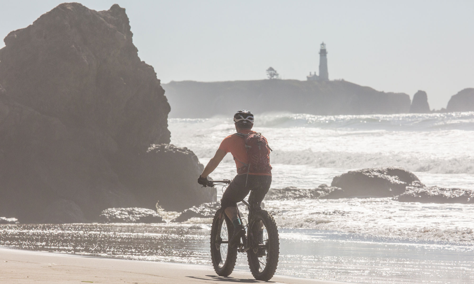A fat biker approaches rocks on the shoreline, with the lighthouse in the background.