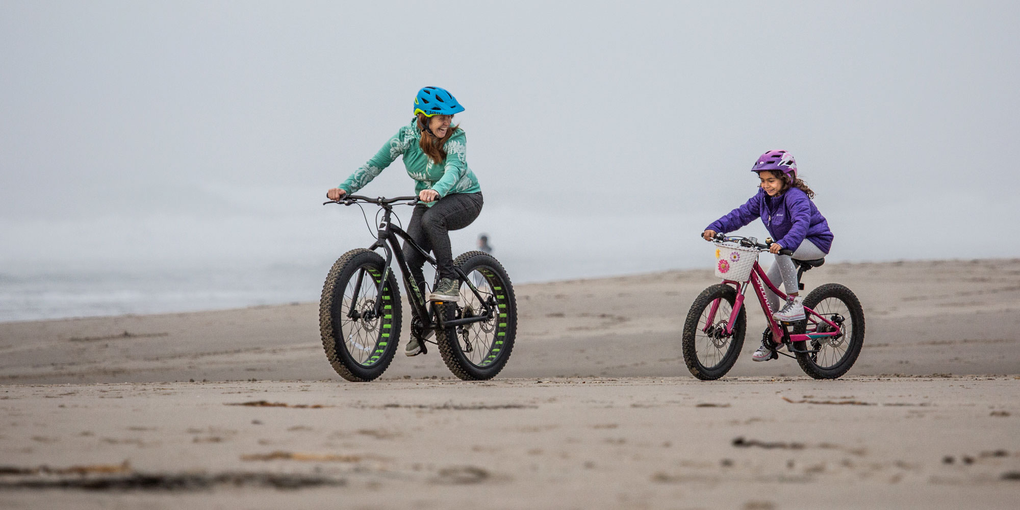 A woman and girl laugh as they ride fat bikes on the sand.