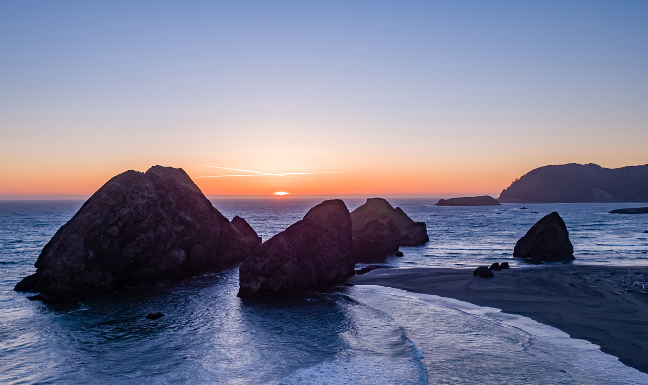 The sun disappears over the ocean horizon and large rock formations at Myers Creek Beach.