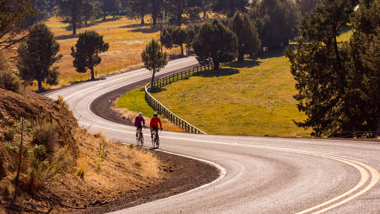 Two cyclists pedal along a scenic winding road in Central Oregon.