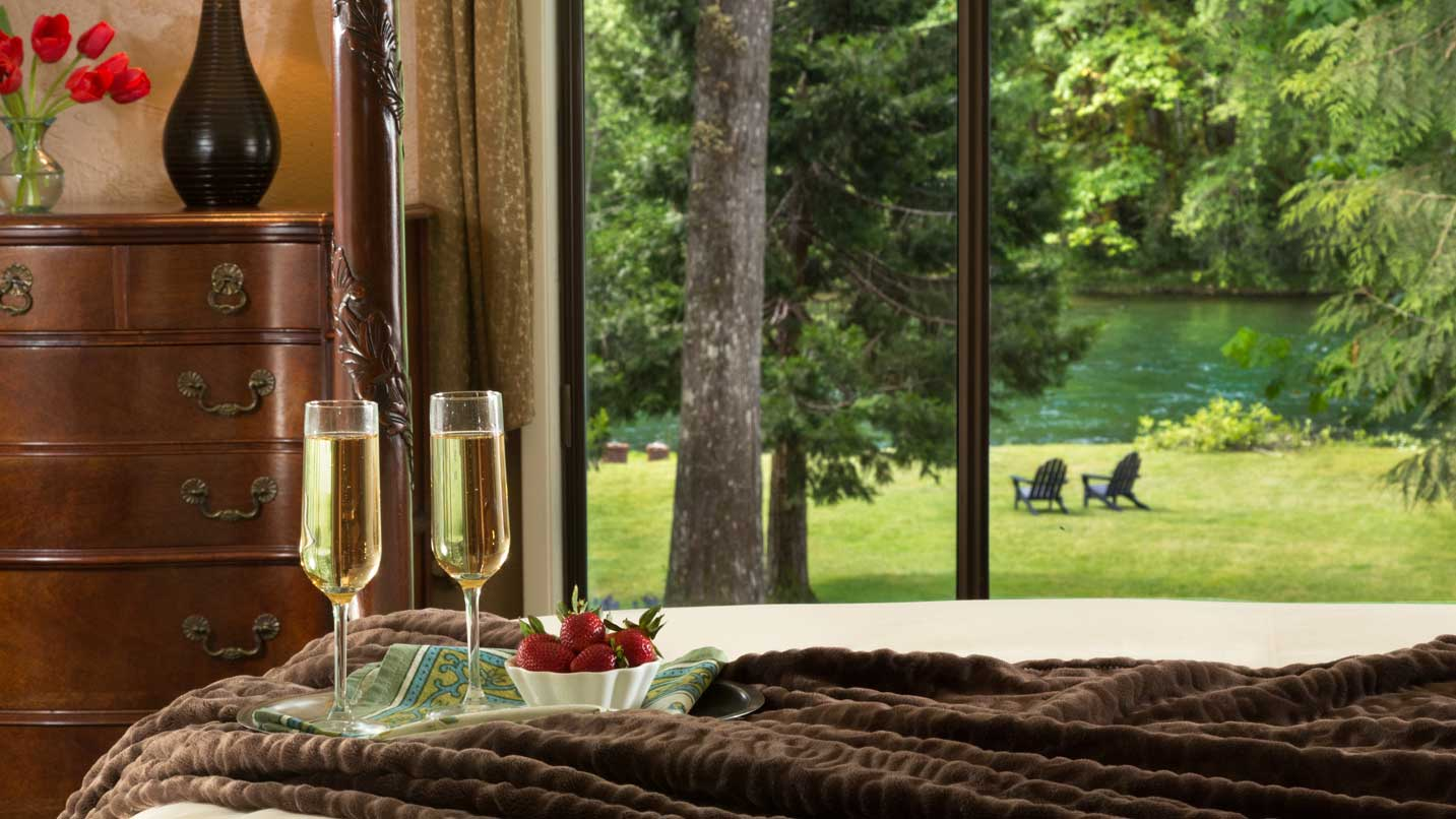 Two champagne glasses sit on a bed overlooking the river.