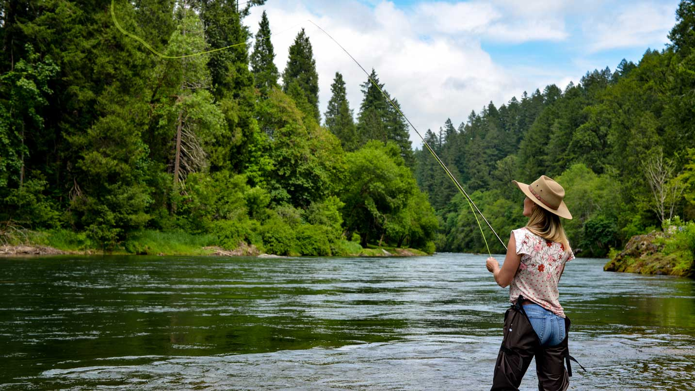 A woman fly fishes on the river.