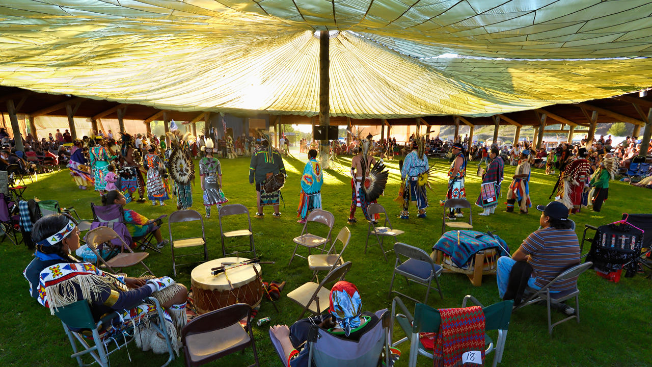 Dancers gather under a large, light-filled tent at the Tamaliks Celebration.