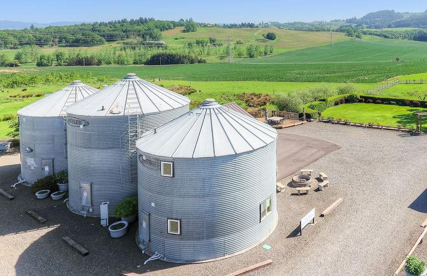 Arial view of three silos on a lush green farm
