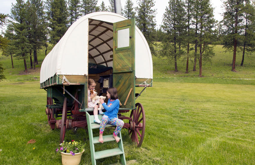Two children sit on the stairs of a covered wagon