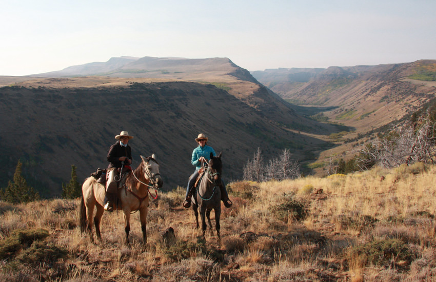 Two horseback riders stop to pose for the camera on the edge of a canyon