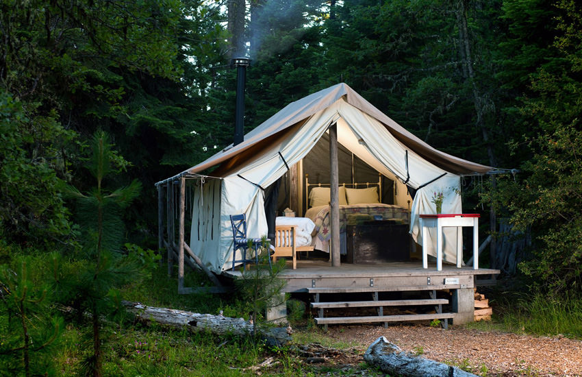 An outdoor walled platform tent, furnished with a bed and chairs, sits in a forest