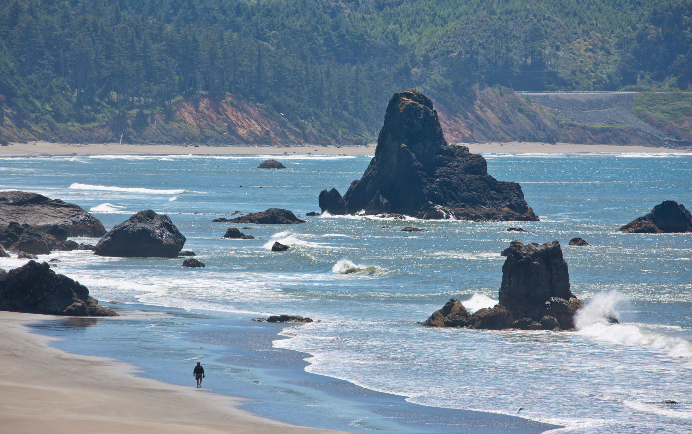A person walks along the beach of Port Orford, ,where sea stacks tower near the shore.