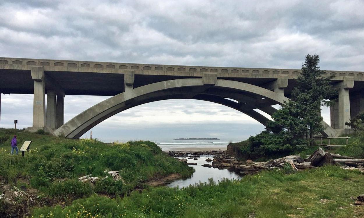 A camper reads an interpretive sign next to a coastal bridge.