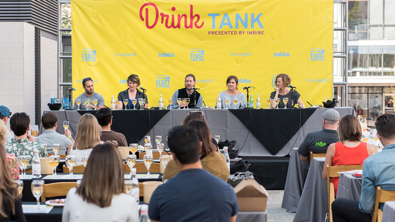 A panel sits in front of a bright yellow Drink Tank banner.