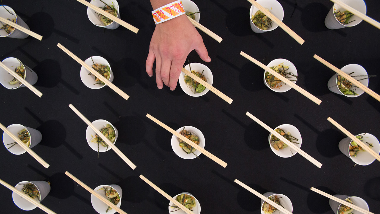 A hand reaches for one of the dishes decorated with chopsticks.