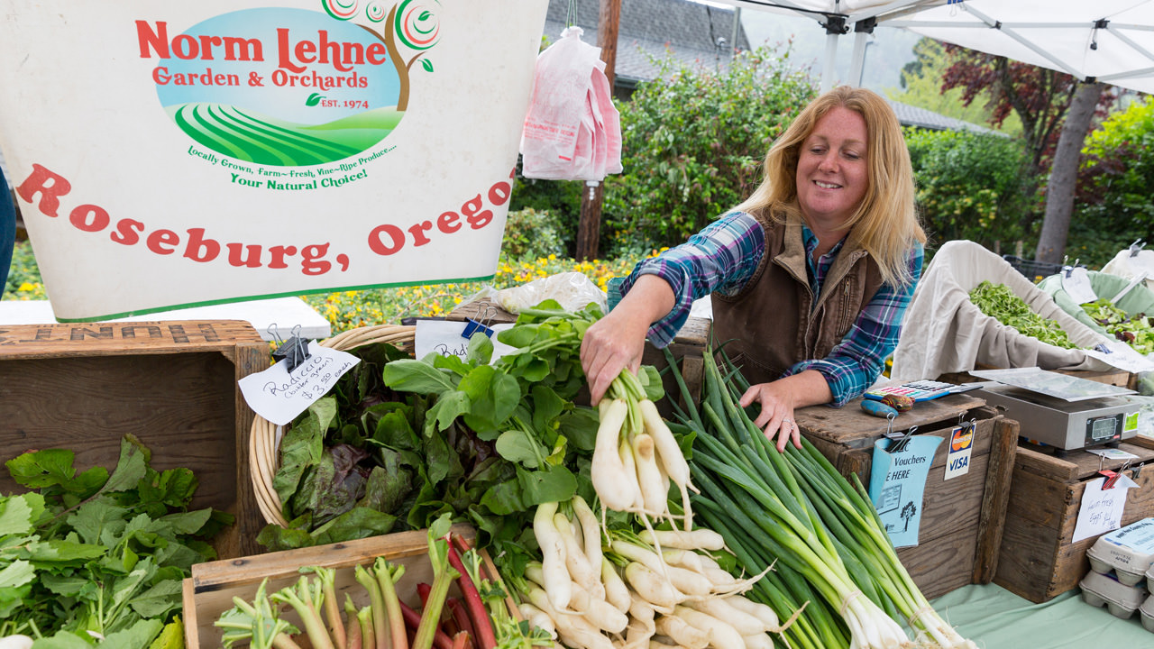 A farmer from Norm Lehne Garden & Orchards grins proudly at her produce during the Umpqua Valley Farmers Market, located on the Great Umpqua Food Trail