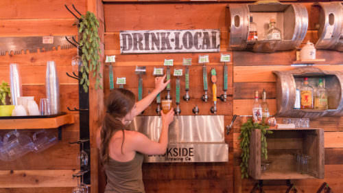 "A bartender pours beer under a ""drink local"" sign at Backside Brewing, one of the stops on the Great Umpqua Food Trail."