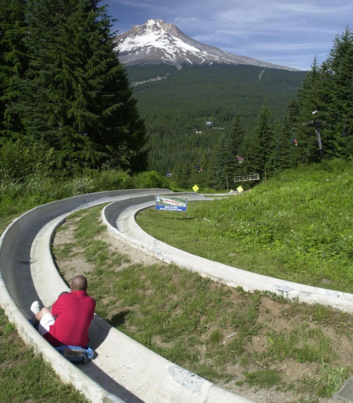 A man goes down the alpine slide with Mt. Hood's peak in the background.