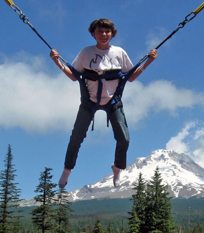 A youth jumps in a bungee in front of Mt. Hood's peak.