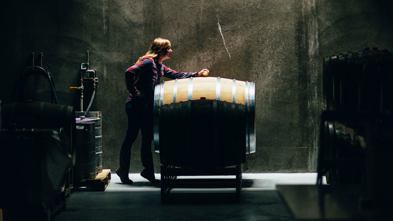 A winemaker inspects a barrel in the shadows.