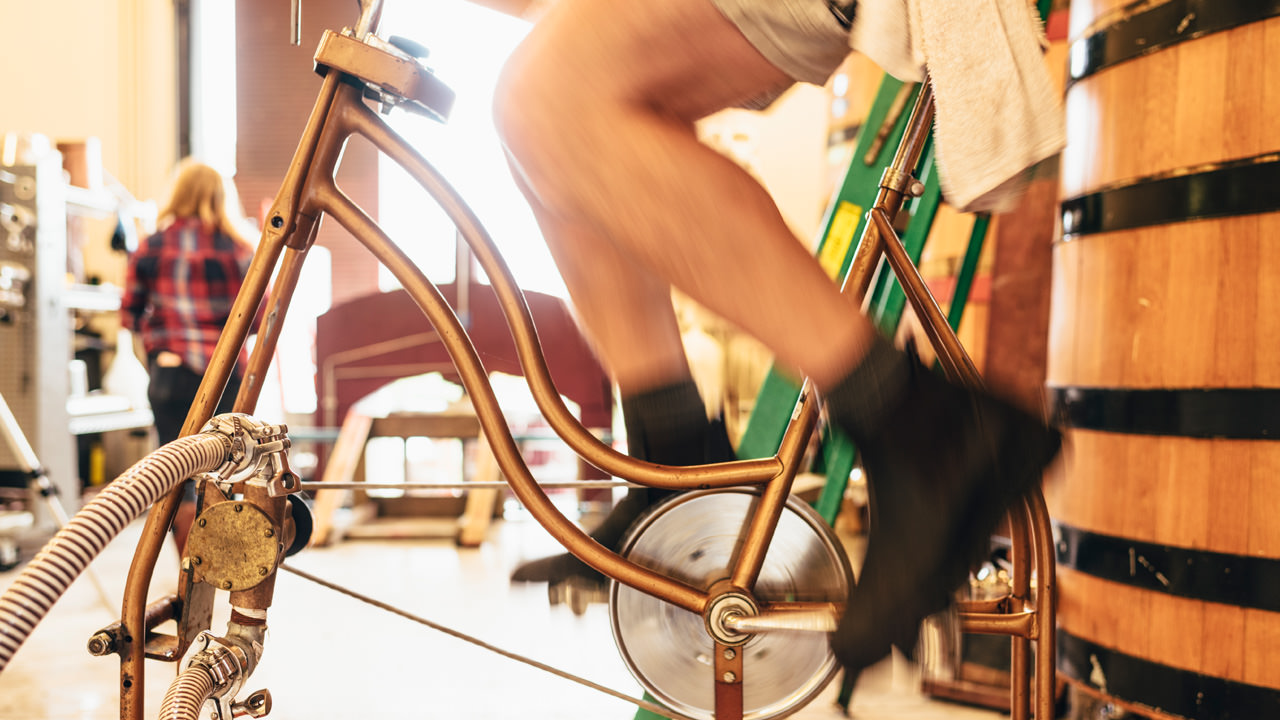 A winemaker pedals an old-school bike to generate energy.
