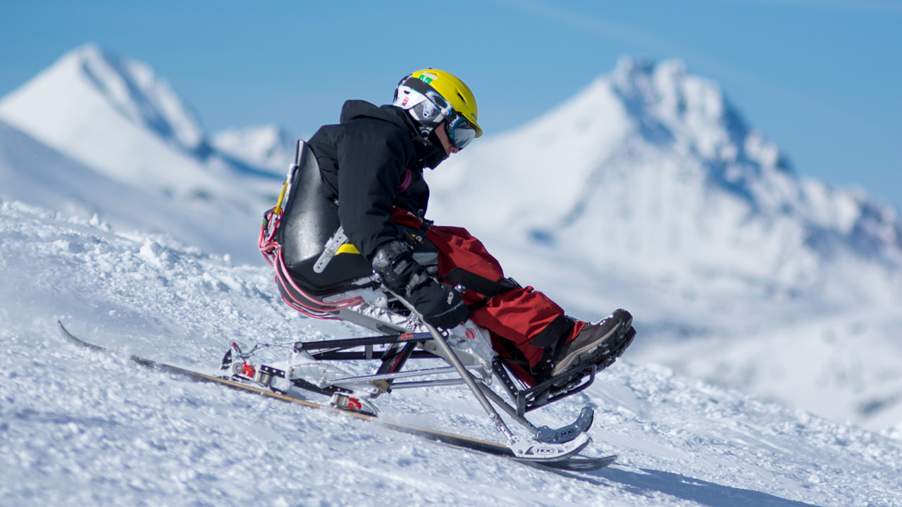 An athlete on adaptive skis heads on a downhill slope.