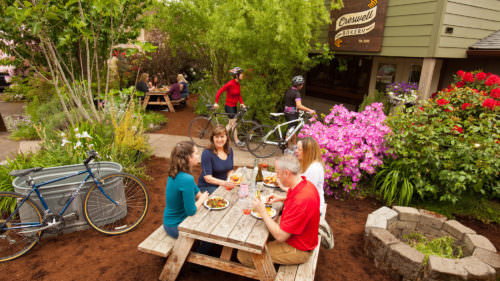 Patrons happily eat on outdoor picnic tables as bicyclists head to the entrance of Creswell Bakery.