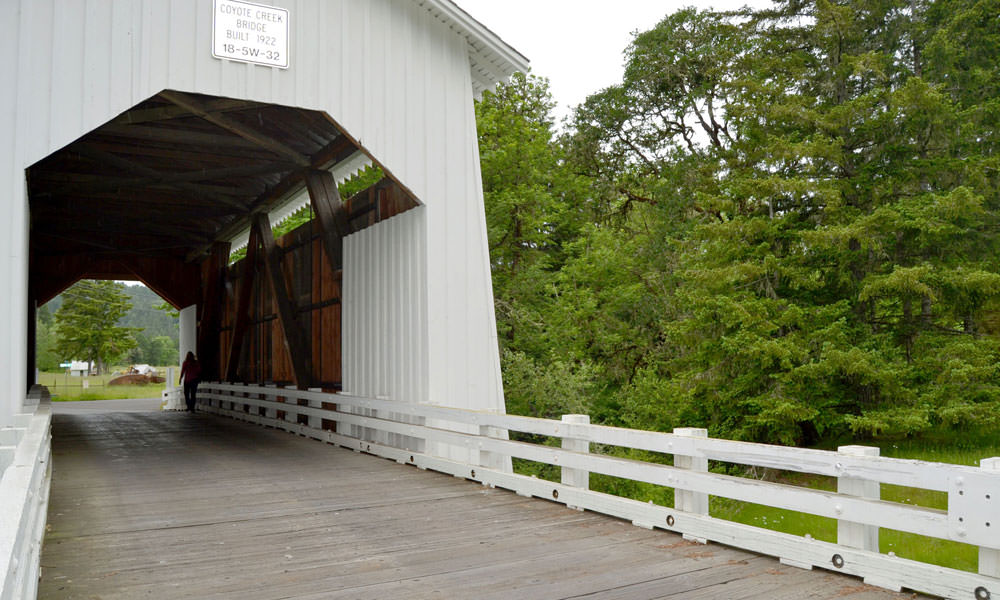 A pedestrian walks on the Coyote Creek Covered Bridge.