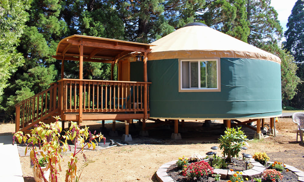 A blue yurt with a wooden deck looks inviting to travelers.