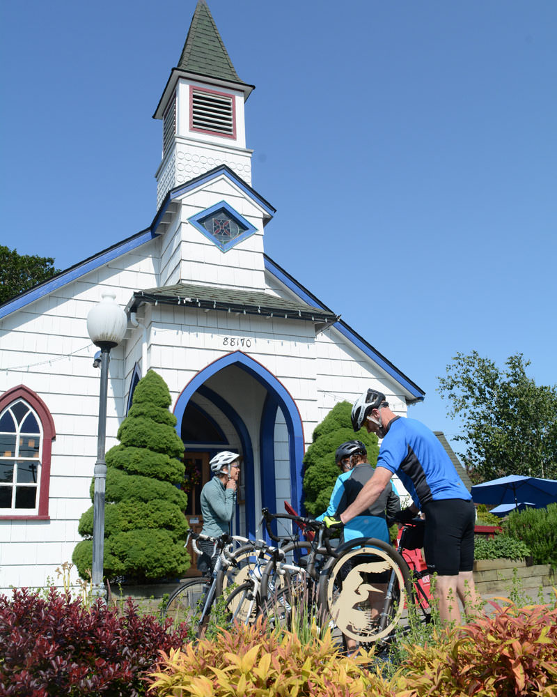 Bicyclists pull up to the entrance of Our Daily Bread, housed in a renovated church.