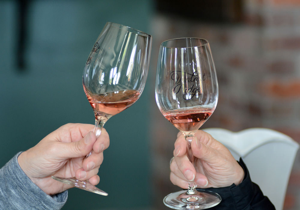 Two people cheers their glasses of Brigadoon rose wine.