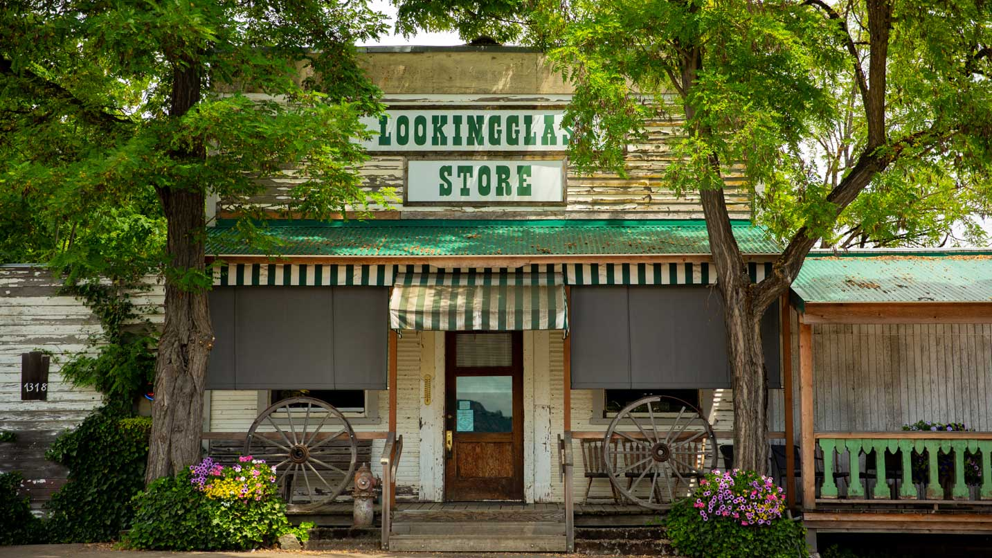 The exterior of the Lookingglass Store features vintage wagon wheels.