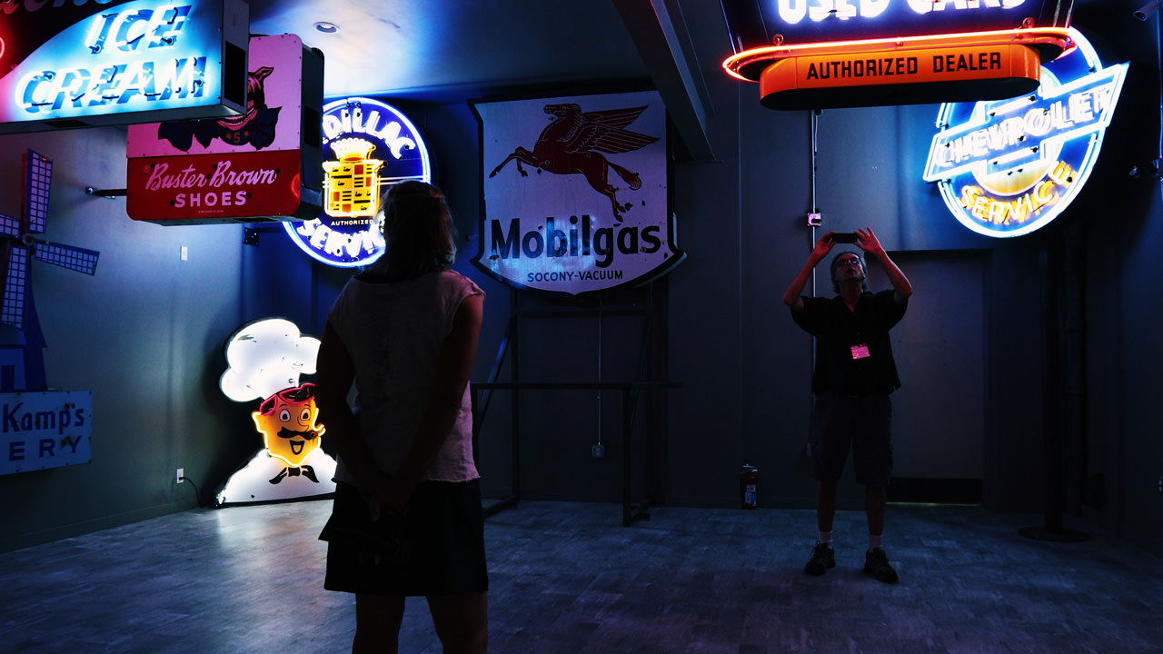 Illuminated by neon signs, two museum patrons view the nostalgic pieces that include Mobilgas, Buster Brown Shoes, Chevrolet and more.