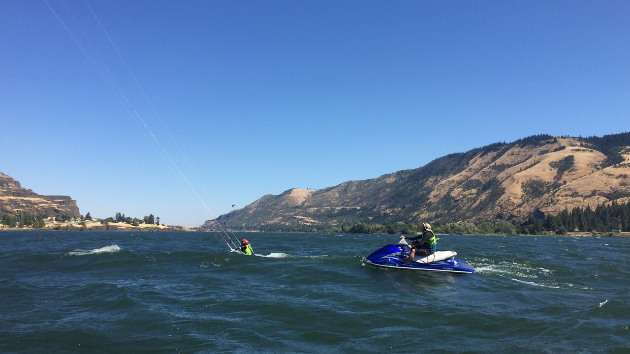 A person on a jet ski follows a beginner kiteboarder on the Columbia River.