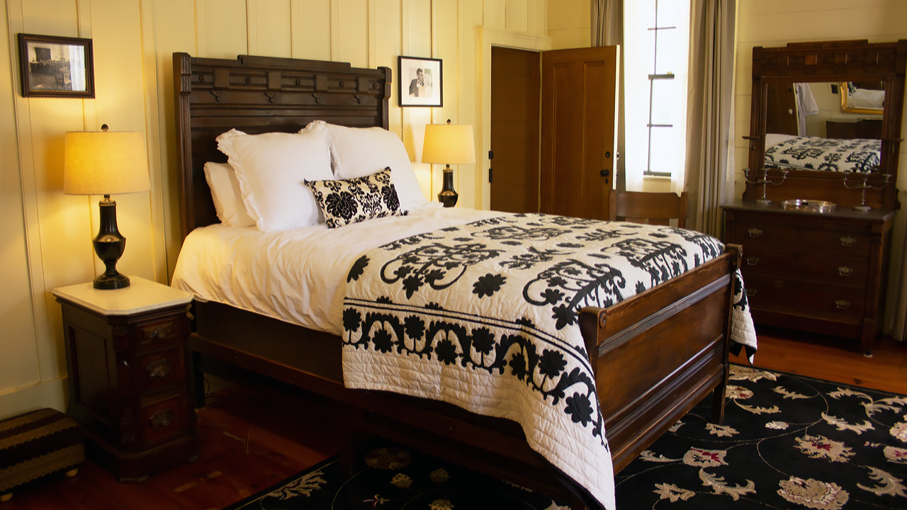 A handmade quilt sits atop a classic bed with dark wooden frame.