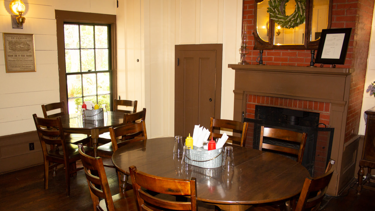 The Wolf Creek Tavern dining room features classic decor, including a brick fireplace.