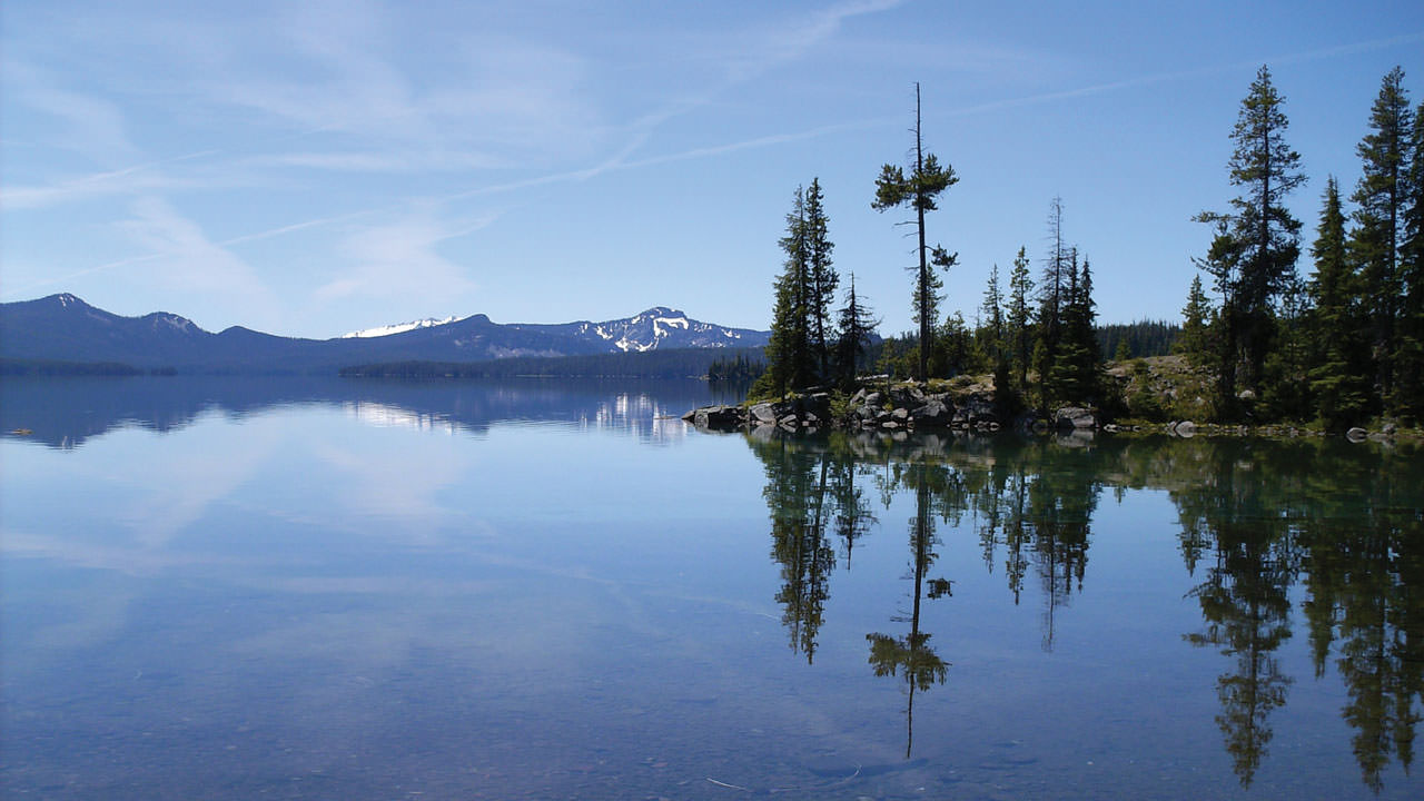 The clear blue waters of Waldo Lake reflect the sky.