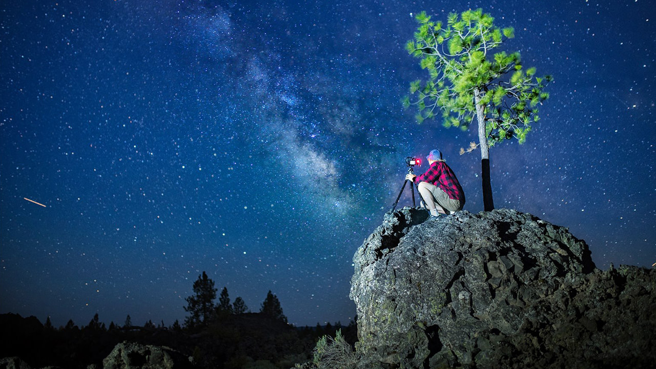 A photographer looks up at the night sky.
