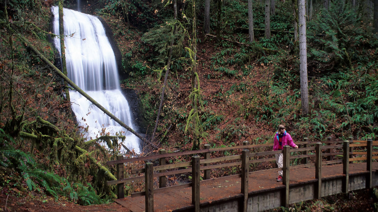 A hiker crosses the footbridge in front of Royal Terrace Falls, likely close enough to feel the waterfall mist.