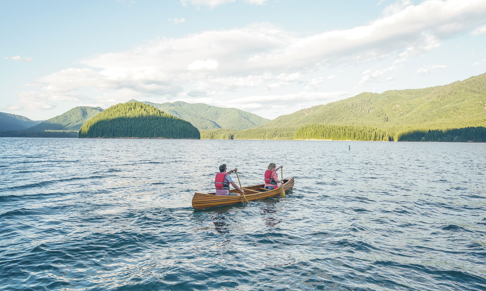 Two people paddle a canoe in a blue-water lake.