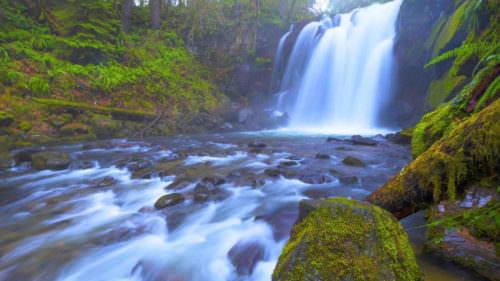 A long exposure photo of a waterfall shows white cascades and mossy rocks.
