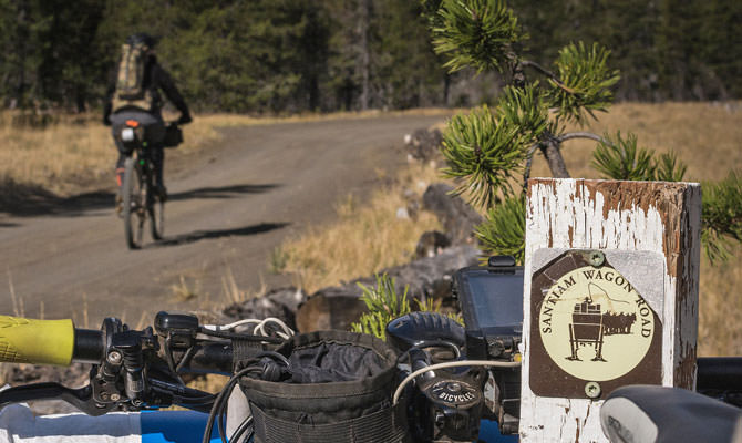 Foreground shows bike gear and the sign for Santiam Wagon Road, with a bicyclist pedaling in the background.
