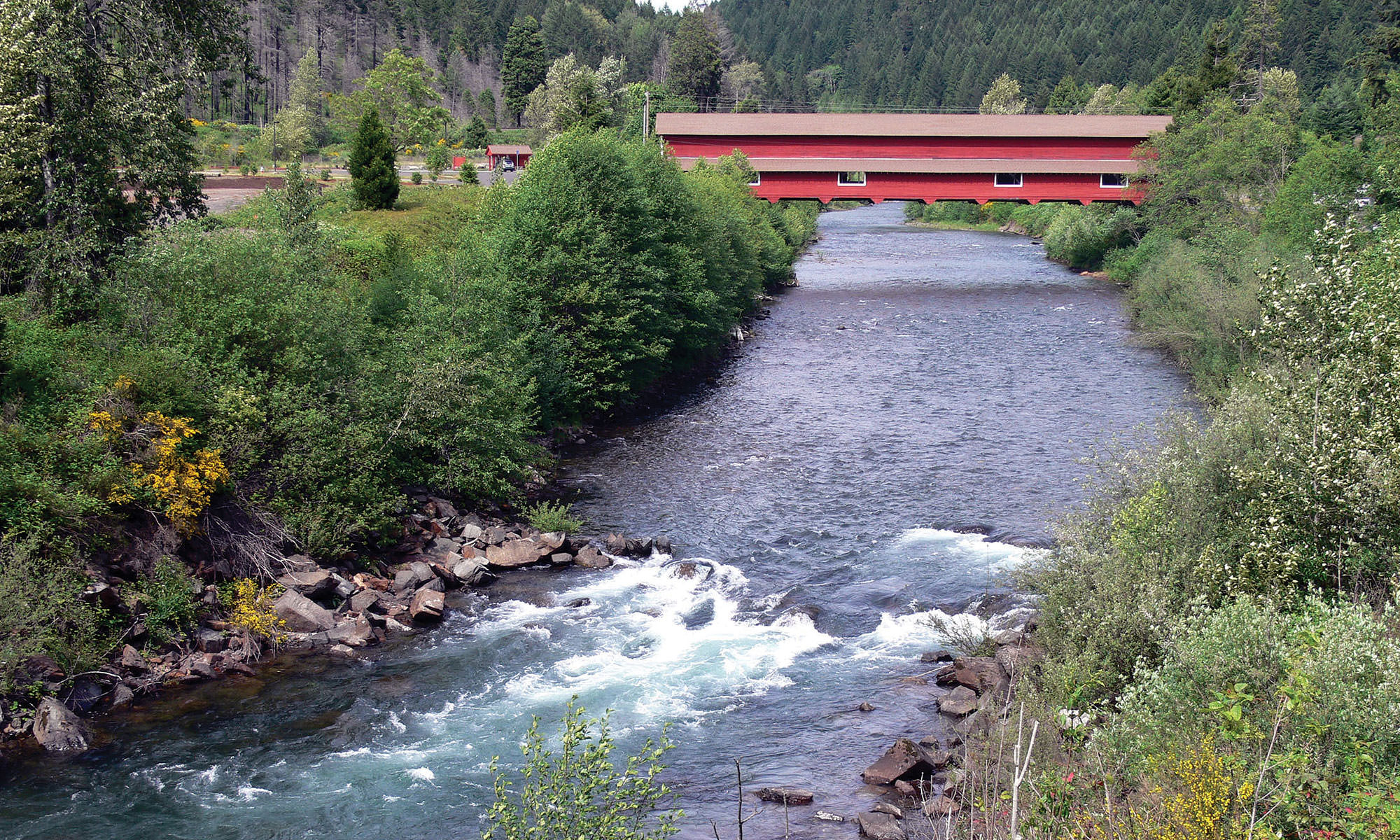 A long red covered bridge spans over a rushing river.