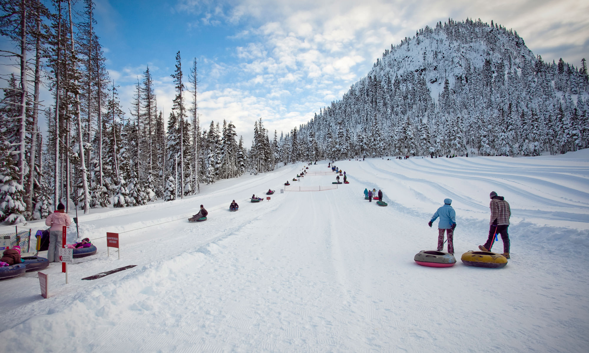 Tubers line up to slide down the snowy hill on a blue-sky day at Hoodoo Ski Area.