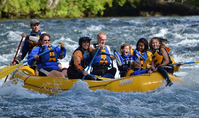 Rafters laugh in delight as they paddle the McKenzie River.