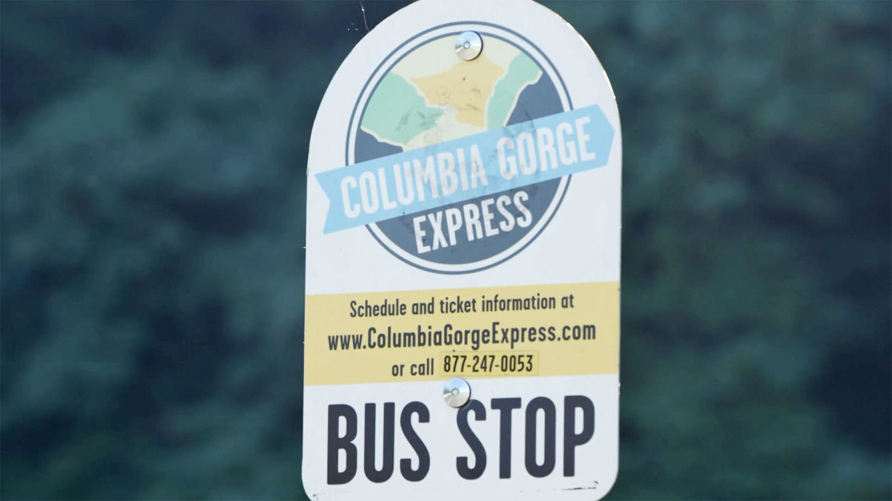 A bus stop sign for the Columbia Gorge Express includes the website ww.ColumbiaGorgeExpress.com